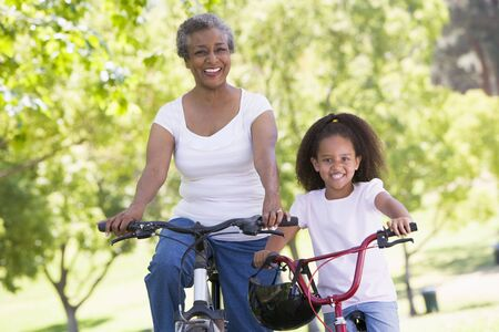 Grandmother and granddaughter on bikes outdoors smiling Stock Photo - 3460185