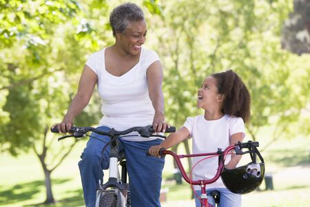 Grandmother and granddaughter on bikes outdoors smiling photo