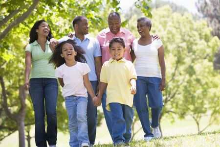 Extended family walking in park holding hands and smiling Stock Photo