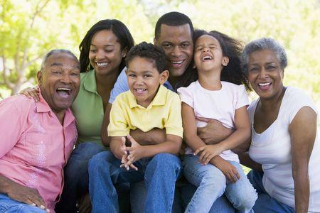 Estensione famiglia seduta all'aperto sorridente Archivio Fotografico