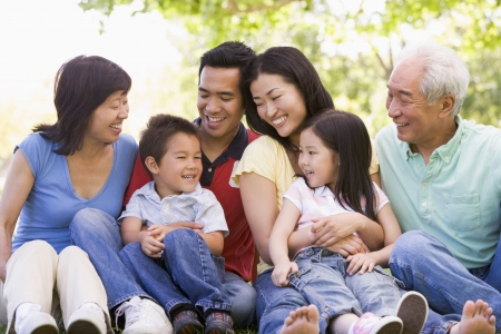 multi generation: Extended family sitting outdoors smiling Stock Photo