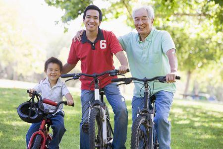 grandchild: Grandfather son and grandson bike riding.