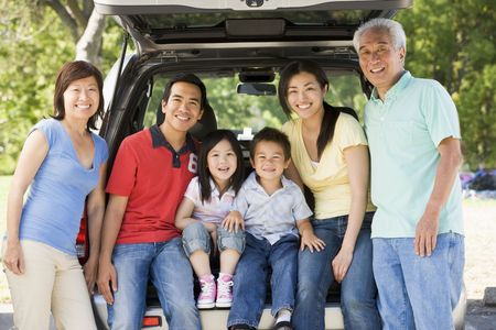 Extended family sitting in tailgate of car photo