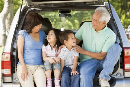 Grandparents with grandkids in tailgate of car photo