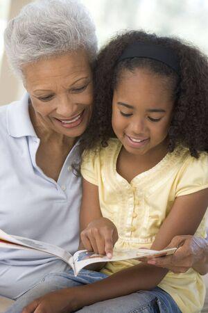 abuelos: Abuela y nieta de la lectura y sonriente  Foto de archivo