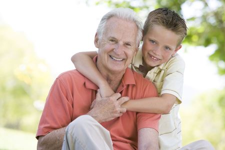 Grandfather and grandson outdoors smiling photo