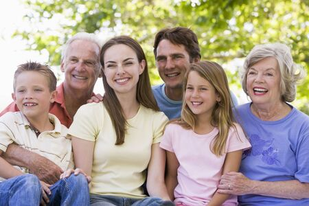 Extended family sitting outdoors smiling photo