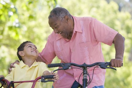 Grandfather and grandson on bikes outdoors smiling photo