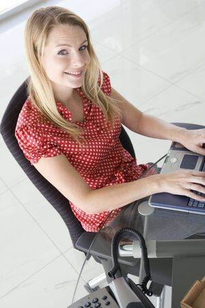 offset angle: Businesswoman sitting in office typing on laptop smiling