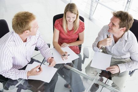 Three businesspeople in a boardroom looking at paperwork photo