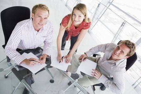 Three businesspeople in a boardroom with paperwork smiling photo