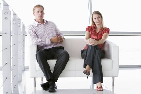 Two businesspeople sitting in office lobby smiling photo