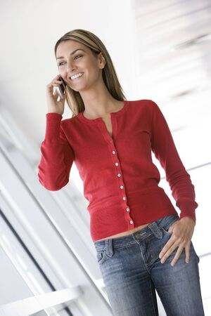 offset view: Woman standing in corridor using cellular phone smiling