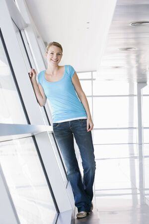 early thirties: Woman standing in corridor smiling Stock Photo