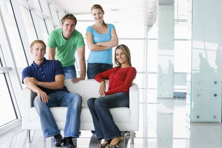 employees group: Four people in lobby smiling