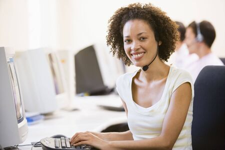 Woman wearing headset in computer room smiling photo