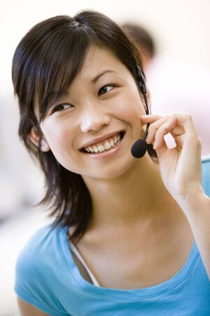 Woman wearing headset indoors smiling photo