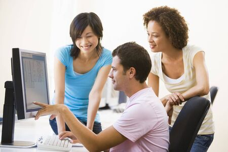 mid twenties: Three people in computer room pointing at monitor and smiling Stock Photo