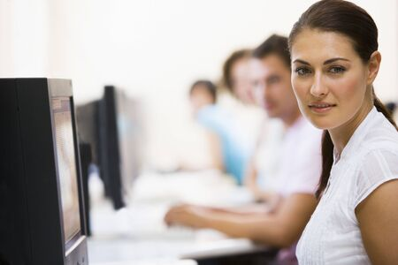 generation x: Woman sitting in computer room with people in background