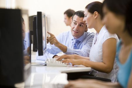 Man assisting woman in computer room photo