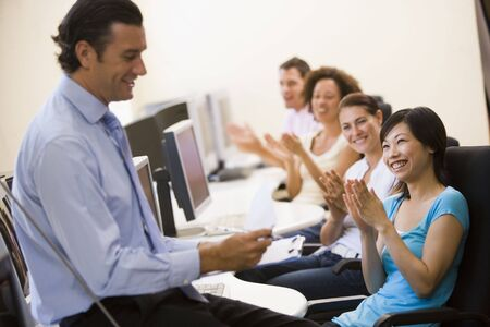 Man with clipboard giving lecture in applauding computer class photo