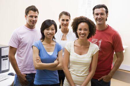 Cinq personnes debout dans la salle le sourire