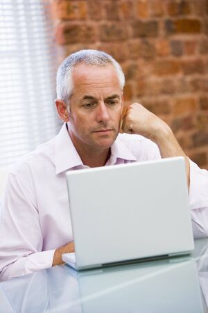 Businessman sitting in office on laptop photo