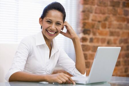 Businesswoman in office with laptop laughing photo