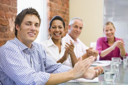 applauding: Four businesspeople in boardroom applauding and smiling