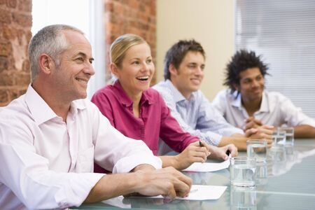 casual caucasian: Four businesspeople in boardroom smiling Stock Photo