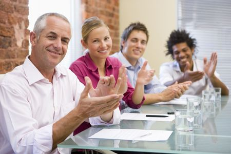 Four businesspeople in boardroom applauding and smiling Stock Photo - 3471044
