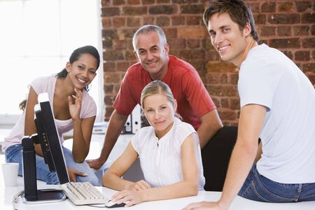 Four businesspeople in office space smiling Stock Photo - 3471670