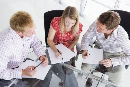Three businesspeople in boardroom with paperwork photo