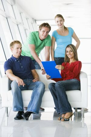 Four people in lobby pointing at clipboard smiling photo