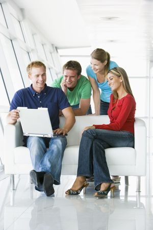 Four people in lobby looking at laptop smiling photo