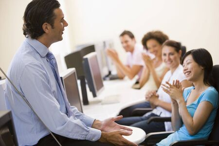 generation x: Man giving lecture in applauding computer class Stock Photo