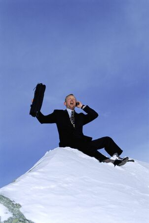 conquering: Businessman outdoors on snowy mountain using cellular phone and yelling