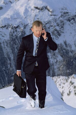 Businessman outdoors on snowy mountain using cellular phone photo