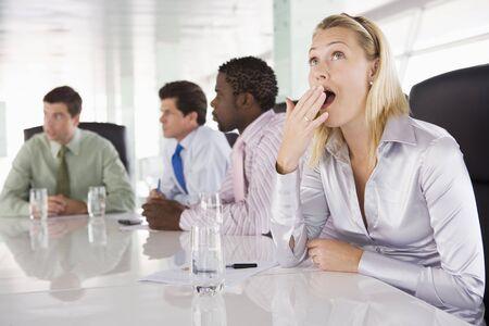 Vier Geschäftsleute im Sitzungssaal mit ein Gähnen Geschäftsfrau
