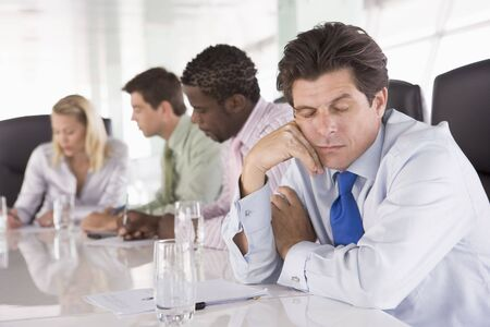 Four businesspeople in boardroom with one businessman sleeping photo
