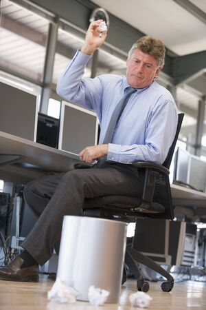 bad idea: Businessman in office space throwing garbage in bin