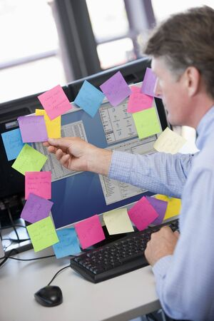 Businessman in office at monitor with notes on it Stock Photo - 3460831
