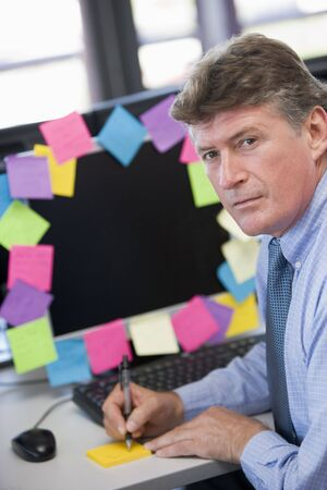 Businessman in office at monitor with notes on it writing Stock Photo - 3461277