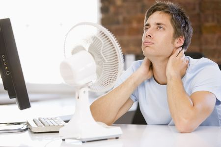 air conditioning: man in office with computer and fan cooling off