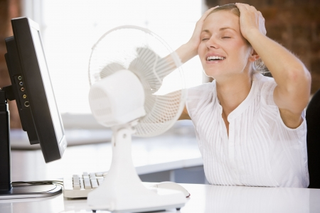 electric fan: Businesswoman in office with computer and fan cooling off Stock Photo