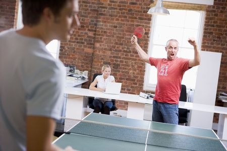 casual office: Two men in office space playing ping pong