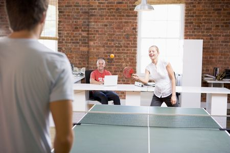 tennis tournament: Man and woman in office space playing ping pong