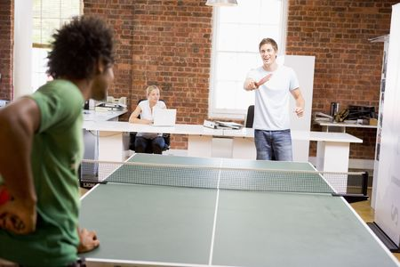 table tennis: Two men in office space playing ping pong