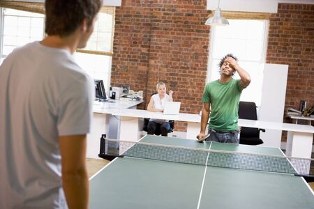 ping pong: Two men in office space playing ping pong