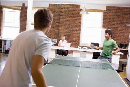 matches: Two men in office space playing ping pong